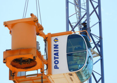 The slew ring and operator cab of a Potain MDT 178 being lowered during a dismantling.